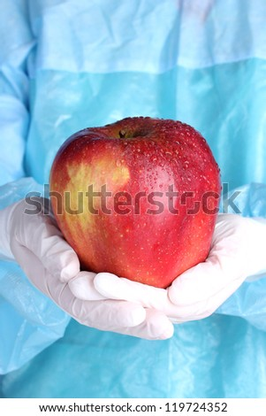 A scientist holds a genetically modified apple - stock photo