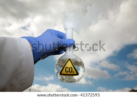 a Scientist holds a 500ml beaker filled with CO2 gainst the blue sky, representing  A Global Warming Time Bomb - stock photo