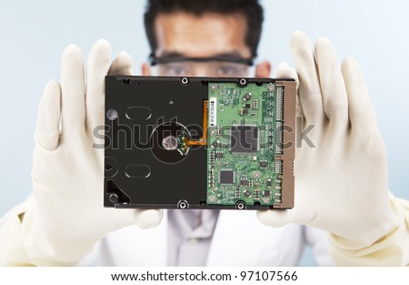 A scientist showing a computer harddisk shot in laboratory