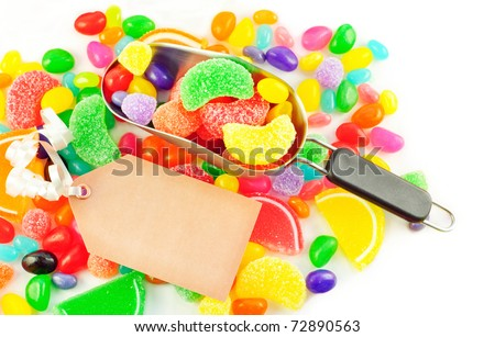 A scoop filled with colorful assorted jelly candies with blank gift tag and candy background - stock photo