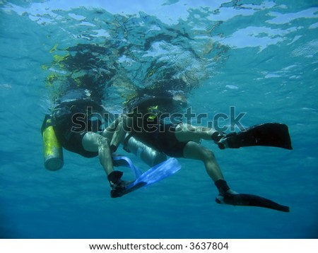 a scubadiver pulls his buddy during a drill - stock photo