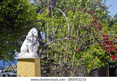 A sculpture of lion by the bougainvillea on sunny day in tropical country