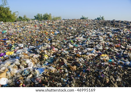 A sea of garbage starts to invade and destroy a beautiful countryside scenery - stock photo