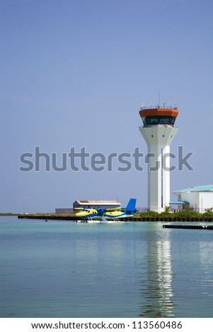 A sea plane lands on the water with the air traffic control tower in the background. - stock photo