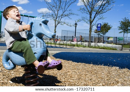 A seahorse bucks a riding toddler at the playground in landscape orientation - stock photo