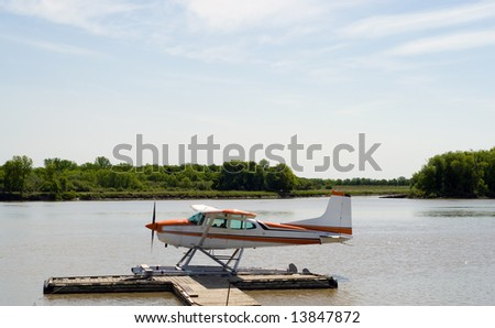 A seaplane parked along a wooden dock on the river - stock photo