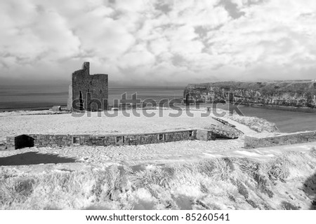a seasonal snow covered view of atlantic ocean and ballybunion castle beach and cliffs on a frosty snow covered winters day in black and white - stock photo