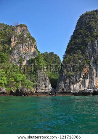 A secluded cove off the coast of Thailand. Emerald water lapping at the cliffs