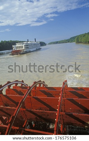A second steamboat paddles down the Mississippi ahead of the Delta Queen's paddle wheel