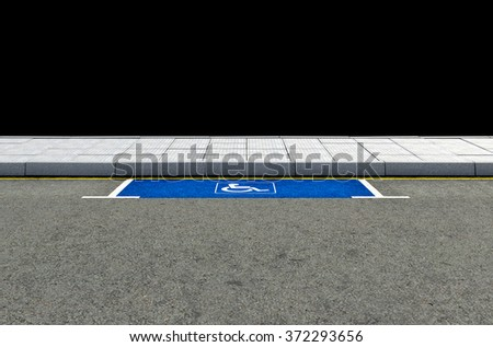 A section of a tarmac road with an empty demarcated paraplegic parking area - stock photo