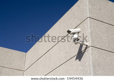 A security camera watches over a building - stock photo