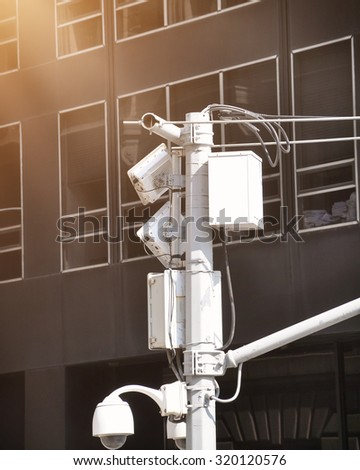 A security video surveillance camera is high in the sky with a city building in the background for a safety concept - stock photo