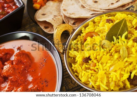 A selection if Indian foods, or a banquet, with pillau rice, chapatis, channa dhal, chicken jalfrezi, rogan josh. - stock photo
