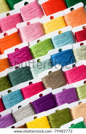 A selection of brightly coloured cotton threads on bobbins - stock photo