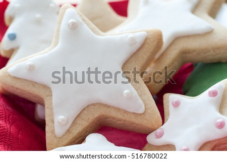A selection of Christmas shaped biscuits with Star shapes in the foreground, decorated with white icing and pearly balls with red napkin.