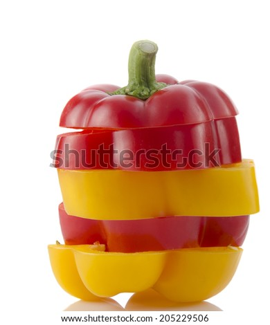 A selection of colorful sweet peppers sliced in pieces to make one pepper on white background