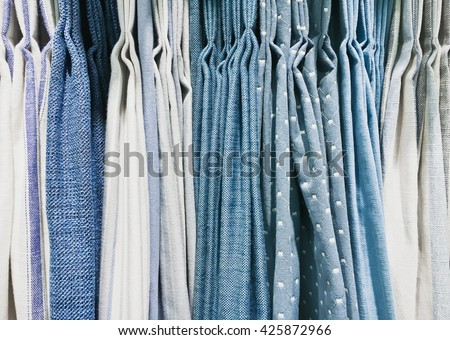 A selection of curtain fabrics in blue and green tones - stock photo