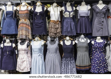 A selection of dresses on sale on a market stall on dummies