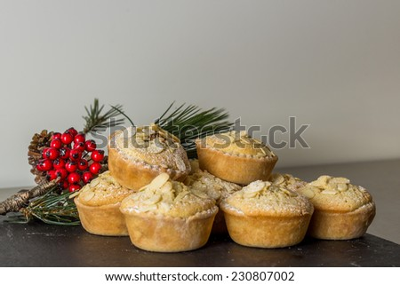 A selection of homemade mince pies with winter berries - stock photo