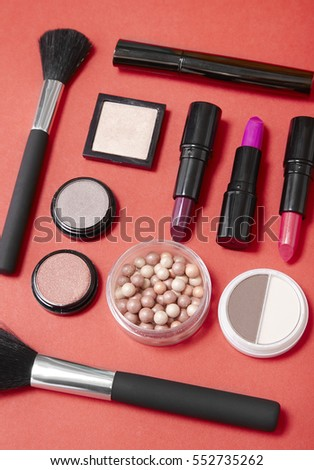 A selection of make up products arranged on a bright red background