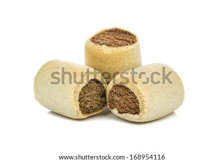 A selection of round roll shaped dog biscuits on a white background - stock photo
