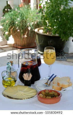A selection of tapas with a jug of Sangria and orange juice, Sliced Manchego cheese, and green olive cocktail, Costa del Sol, Malaga Province, Andalusia, Spain, Western Europe. - stock photo