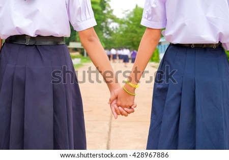 a selective focus picture of clasp hands of thai students mean friendship