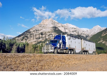 a semi truck going up through the Canadian Rockies with motion blur - stock photo