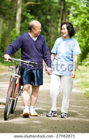A senior active asian couple walking and exercise at the park - stock photo