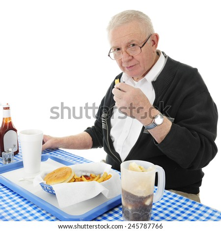 A senior adult man looking up at the viewer as he enjoys a french fry from his fast food basket.  On a white background. - stock photo