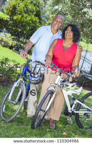 A senior African American woman & man couple riding bicycles in the summer - stock photo