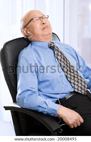 A senior asian businessman sleeping and listening to music at the office - stock photo