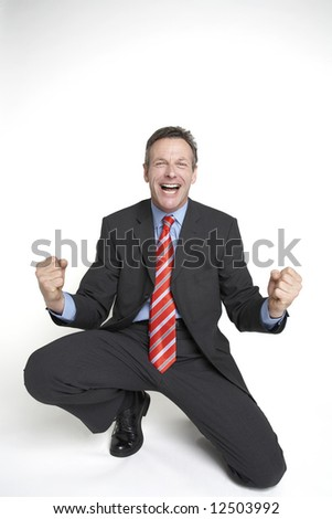 A senior businessman drops to his knees in celebration of a done deal! - stock photo