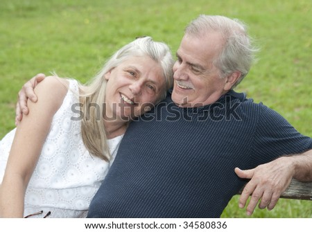 A senior citizen man looks happily at his wife on a casual afternoon. - stock photo