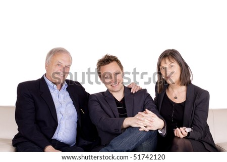 A senior couple and their adult son sitting in the sofa