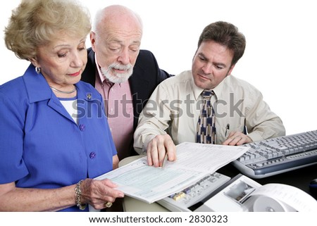 A senior couple going over the tax booklet with their accountant.  Isolated on white. - stock photo