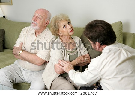 A senior couple in marriage counseling.  They have their backs turned and are ignoring each other while the therapist tries to reconcile them. - stock photo