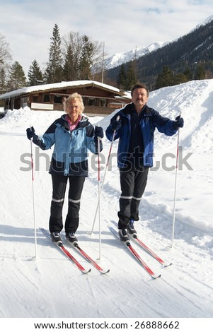 A senior couple outdoor in a winter setting. The active couple is about to go crosscountry skiing. - stock photo