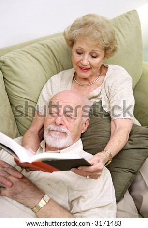 A senior couple reading together.  The wife is reading to the husband. - stock photo