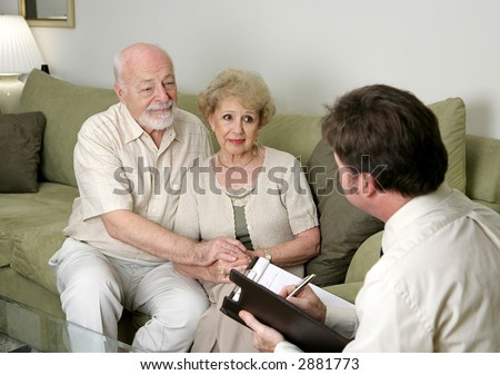 A senior couple talking with a marriage counselor.  Could also be a salesman in their home. - stock photo