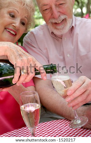 A senior couple - the wife is pouring champagne for the husband.  (focus is on bottle neck & champagne in glass)
