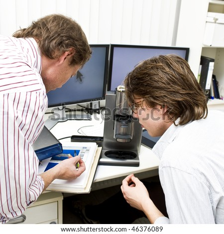 A senior engineer explaining the work to be done to a colleague - stock photo