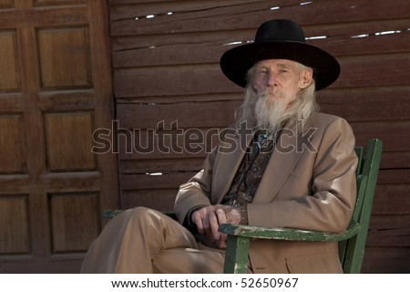 A senior gentleman wearing a western style suit and cowboy hat is sitting in a chair. Horizontal shot. - stock photo