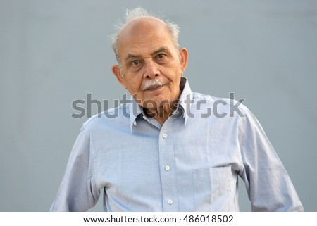 A senior Indian / South Asian man against a light blue background