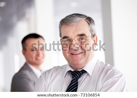 A senior leader looking at camera and smiling with colleague behind - stock photo