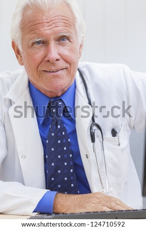 A senior male doctor sitting at a desk in an office with a computer, wearing a shirt, tie and stethoscope - stock photo