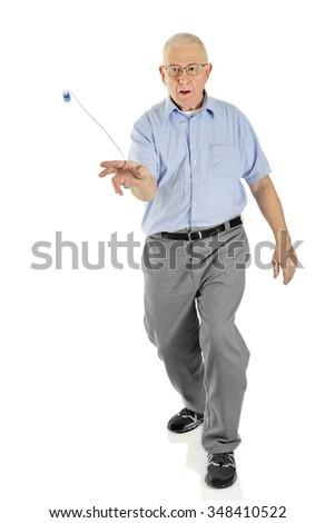 "A senior man concentrating on starting his ""around the world"" yo-yo trick.  On a white background.  Motion blur on yo-yo. - stock photo"