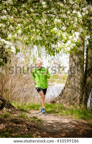 A senior man dressed in black and green is running in the forest, close to the lake, under an apple blossom, during a warm spring day - stock photo