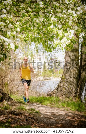 A senior man dressed in black and yellow is running in the forest, close to the lake, during a warm spring day - stock photo
