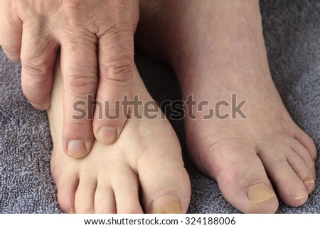 A senior man has a hand on one of his feet.